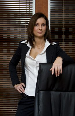Attractive brunette business woman wearing business suit standing next to chair